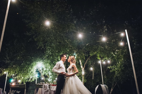 Beautiful newlyweds stand, holding hands, at a wedding party with lamps. Stylish wedding ceremony.