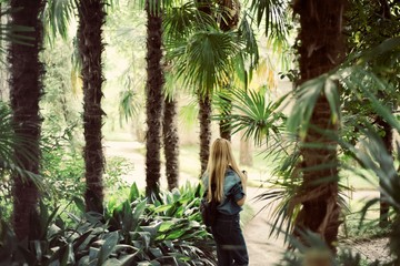 attractive young blonde tourist woman girl in beautiful jungles with camera taking photos, holiday, travel concept