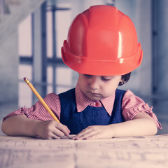 Humorous portrait of cute little child girl engineer in construction helmet working with document and blueprints in office