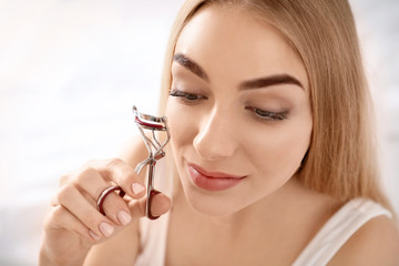 Young woman curling her eyelashes at home