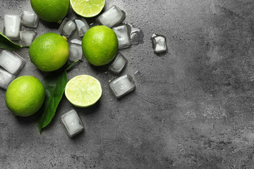 Composition with fresh ripe limes and ice cubes on gray background, top view