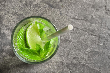Refreshing beverage with mint and lime in glass on grey background, top view