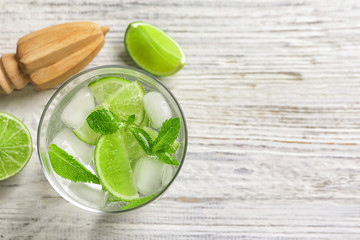Refreshing beverage with mint and lime in glass on wooden background, top view