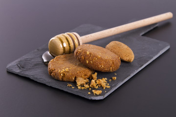 Honey and Cookies on a cardboard shale on a Black Background