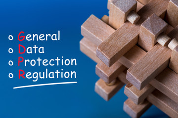 General Data Protection Regulation GDPR - Text on blue background with wooden brain teaser. Data Protection Concept.