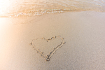 Beautiful background beach with heart in summer. Royalty high-quality free stock image of shape heart draw on the sand and beach