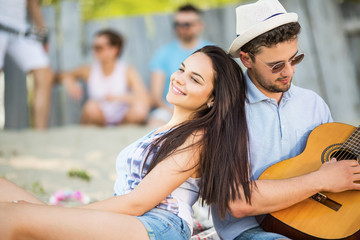 Young couple on the beach playing guitar