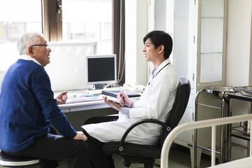 若い医者の診断を受ける老人
