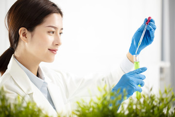 young woman plants scientist watching test tube
