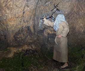 The white-haired hermit in sackcloth painting animals on cave walls.