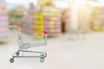 Empty red shopping cart with Abstract blur supermarket discount store product shelves interior defocused background