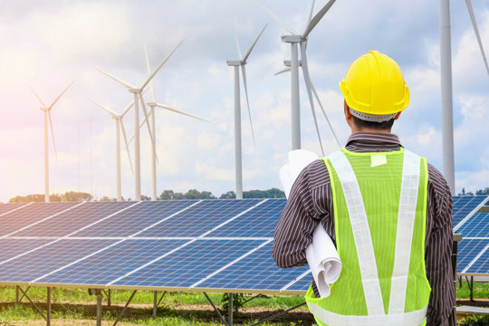 Young business man engineer with yellow helmet at solar panel and wind generators power plant construction site background