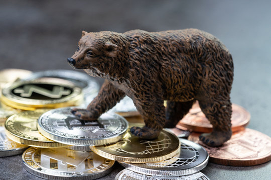Bearish market concept, price down or falling demand collapse of crypto currency, bear figure standing on various of cryptocurrency physical coins, Bitcoin, Ripple, ZCash, Litecoins, Ethereum