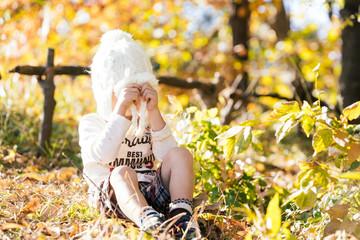 逆光がさす秋の公園で心を閉ざす5才の男の子のイメージ