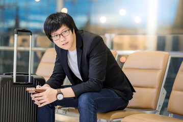 Young Asian well-dressed businessman holding passport sitting on bench near his suitcase luggage while waiting for connecting flight in airport terminal. man in business travel concept