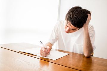 悩んでノートを見つめる男性