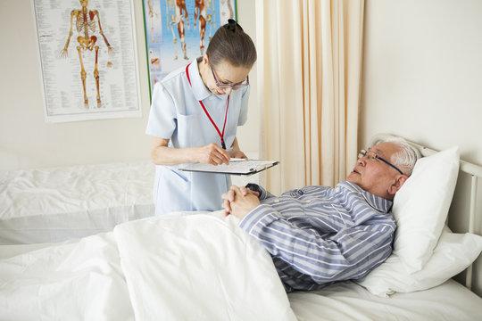 入院患者のバイタルチェックをしている看護師。高齢者。