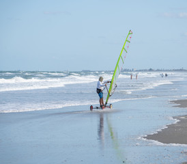 unknown sail boarder rides the beach