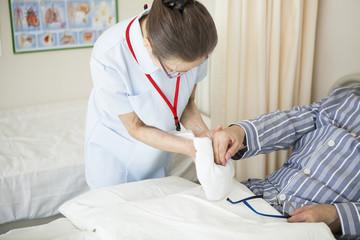 介護士が患者の手を拭いて、ケアをしている。