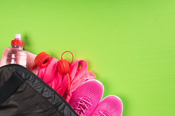 things for sport and a bottle of water in a black bag on the corner of a green board background