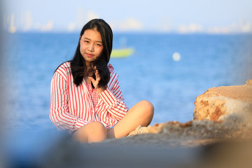 portrait of young asian girl sitting on the stone near the sea