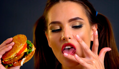 Woman eating hamburger. Girl wants to eat burger. Student received scholarship and dines. Portrait of person with good appetite have greedily dinner delicious sandwich. Expensive fast food restaurant.