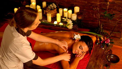Massage of woman in spa salon. Girl on candles background in therapy room. Luxary interior in oriental therapy salon. Female have relax after beauty health procedure.