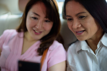 Two mature Asian women together travelling inside the car