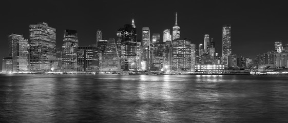 New York City skyline reflected in the East River at night, USA.