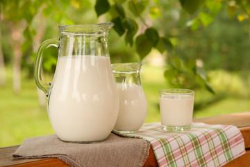 Много молока на фоне сада. Два кувшина и стакан молока на подоконнике деревянной беседки. Молоко в окружении зеленых веток дерева. Молоко в деревенском стиле.