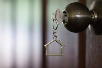 Home key with house keychain in keyhole, property concept