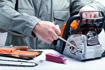 Repair of chainsaws,gasoline powered tools. Man repairing chainsaw.
