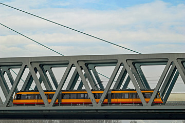Straßenbahn fährt über Eisenbahnbrücke