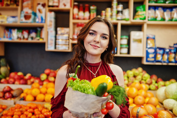 Girl in red holding different vegetables on fruits store.