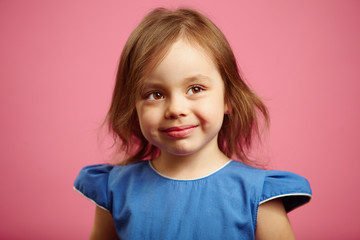Cute little girl is looking above the camera with a wistful glance.