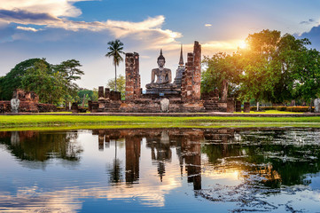 Buddha statue and Wat Mahathat Temple in the precinct of Sukhothai Historical Park, Wat Mahathat Temple is UNESCO World Heritage Site, Thailand.