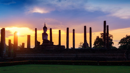 Wall Mural - Silhouette of Buddha statue and Wat Mahathat Temple in the precinct of Sukhothai Historical Park, Wat Mahathat Temple is UNESCO World Heritage Site, Thailand.