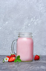 Healthy breakfast. Glass jar of homemade yogurt and fresh strawberries with spring flowers