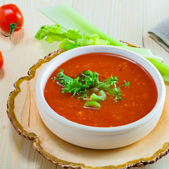 Gazpacho in a bowl, ingredients and bread. Classic Spanish cuisine vegetarian soup.