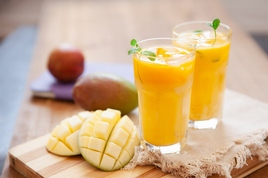Fresh mango smoothie in glass with fruits on the wooden table