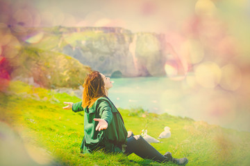 photo of beautiful young woman sitting on the grass and relaxing on the wonderful landmark background