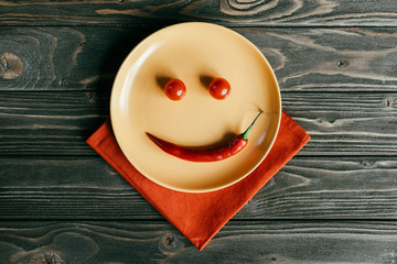 Plate with smile made of pepper and tomatoes on orange napkin