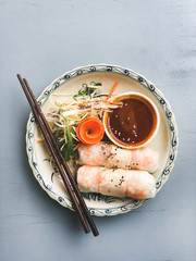 Asian style dinner. Flat-lay of summer rice paper rolls with shrimp and teriyaki sauce in bowl over blue table, top view, copy space. Chinese cuisine