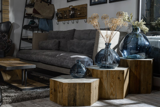 interior of modern retro styled living room with grey sofa and vases on wooden shelves