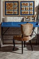 interior of modern retro styled living room with blue table, chair and photos in frames