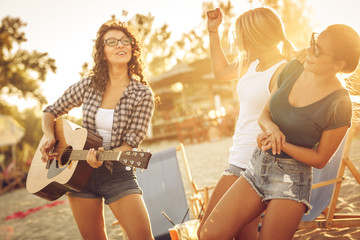Group of young female friends at the beach ,singing and playing guitar.