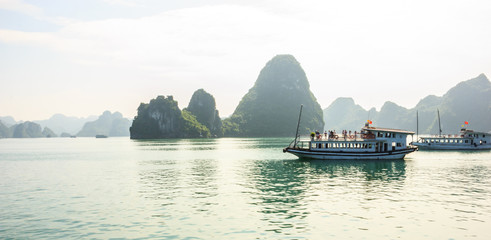Ha Long Bay islands, tourist boats and seascape with light reflection on water, Ha Long, Vietnam.