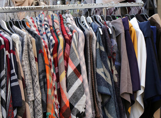 Coat shirts and many used clothes hanging in the stall of the fl