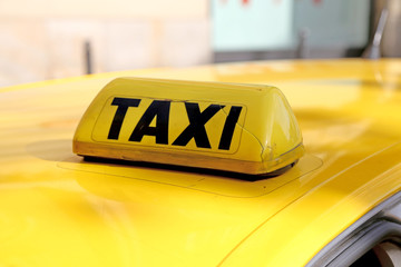 taxi in capital letters above the yellow car