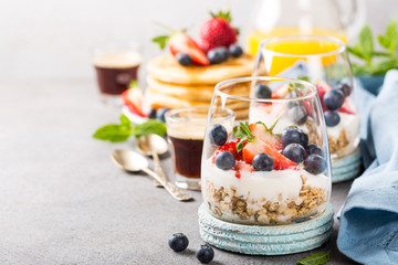 Oatmeal granola with berries and yogurt and panccakes on light gray concrete background. Healthy breakfast food concept with copy space.